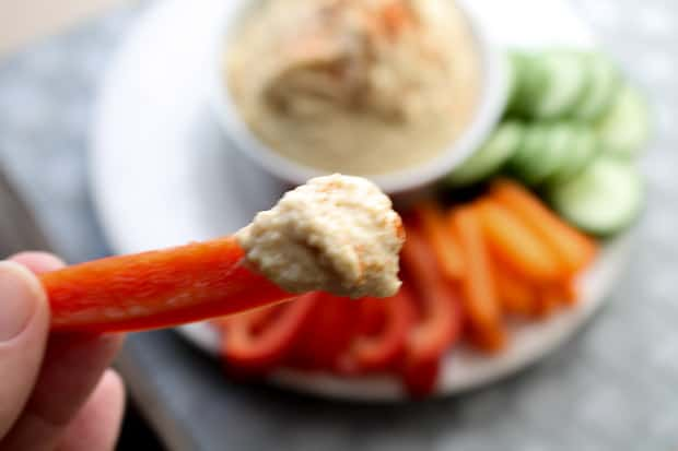 A carrot dipped in hummus