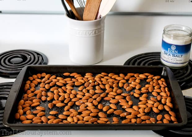 Almonds on a baking sheet sitting on a stovetop