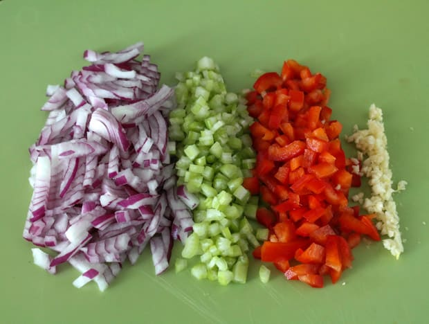 Chopped red onions, celery, bell pepeprs and minced garlic on a green cutting board.