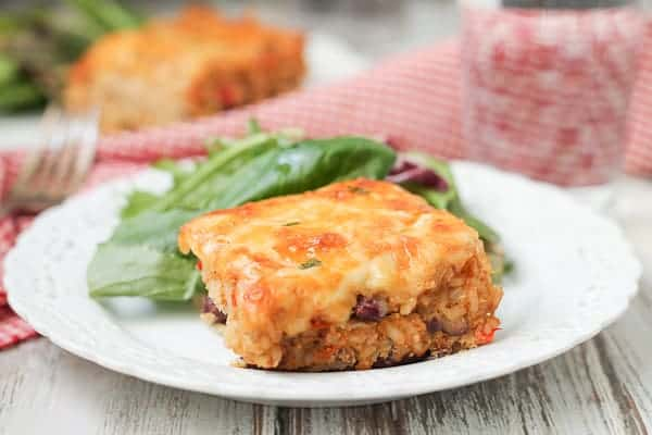 Cheesy casserole on a plate with salad.
