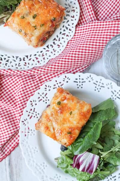 Cheesy casserole on a plate with a side salad and red checkered napkin.