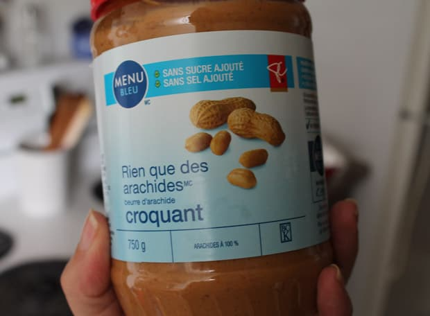 A hand holding a jar of natural peanut butter