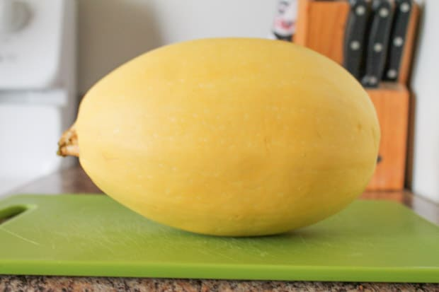 A whole spaghetti squash on a green cutting board