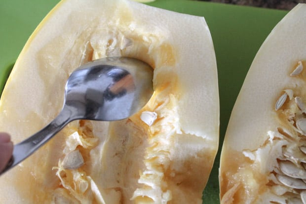A spoon scraping the seeds out of a spaghetti squash