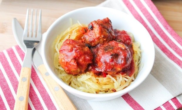 Oven Baked Turkey Meatballs in tomato sauce on a bed of spaghetti squash in a white bowl.