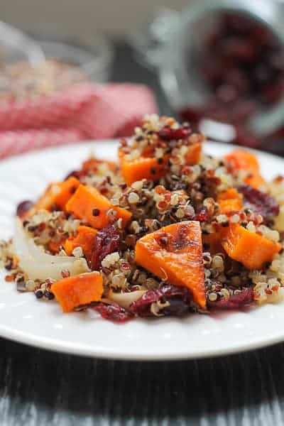 Spicy Roasted Butternut Squash with Quinoa & Cranberries on a white plate with a red checkered napkin in the background