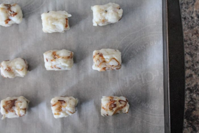 Tater tot cylinders lined up on a baking tray ready to baked