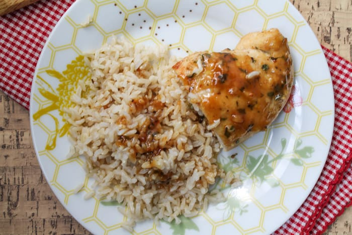 Cooked chicken on a plate with rice, drizzled in sauce