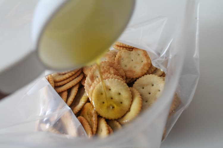 Crackers in a ziploc bag with olive oil being poured overtop