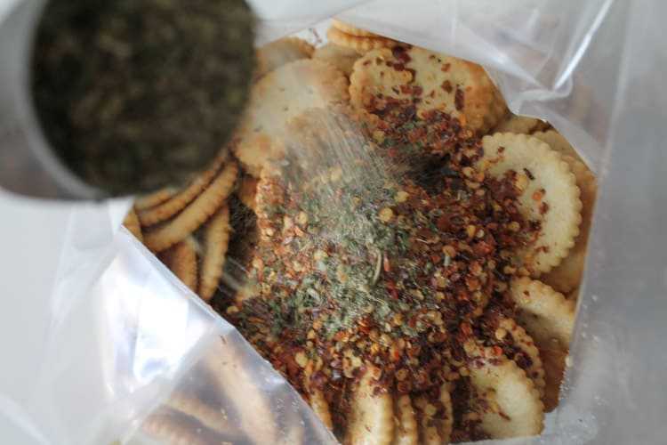 Spices being poured over crackers in a ziploc bag