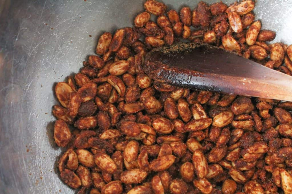 roasted nuts being stirred in a mixing bowl