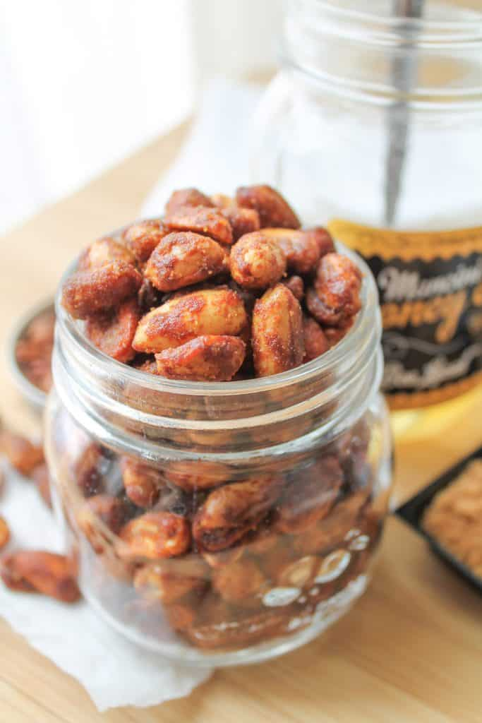 Honey Roasted Peanuts in a glass jar with a jar of honey in the background