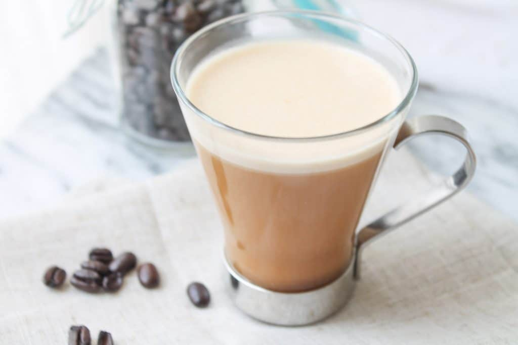 Creamy coffee in a glass mug with coffee beans in the background