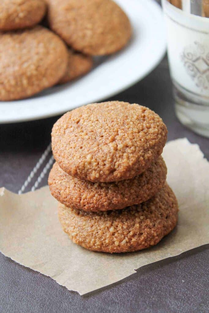 Ginger Almond Cookies on parchment paper with a glass of milk in the background