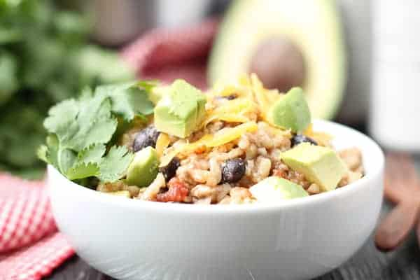 Rice, beans and chicken in a bowl topped with cheese, cilantro and avocado with a red checkered napkin and an Instant Pot in the background
