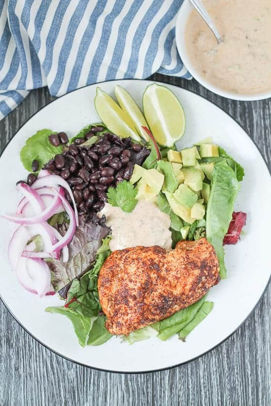 Chipotle Chicken Salad on a white plate with black trim on a dark wood background with a blue striped napkin and a small bowl of dressing behind.