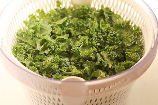 Kale soaking in a salad spinner full of water