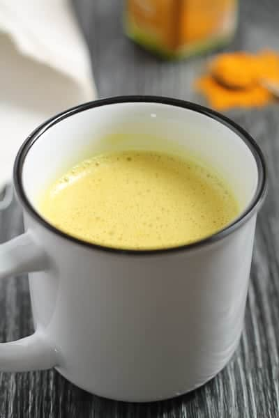 Golden Milk Latte in a white mug on a dark wooden surface with a spoonful of ground turmeric in the background