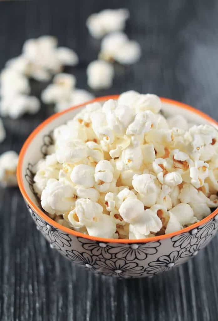 A healthy and inexpensive treat, this Coconut Oil Popcorn recipe will become your go-to snack. So easy to make and customize to your taste buds. #glutenfree #vegan #recipe